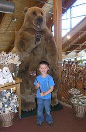 Kid with braces posing in front of fake bear